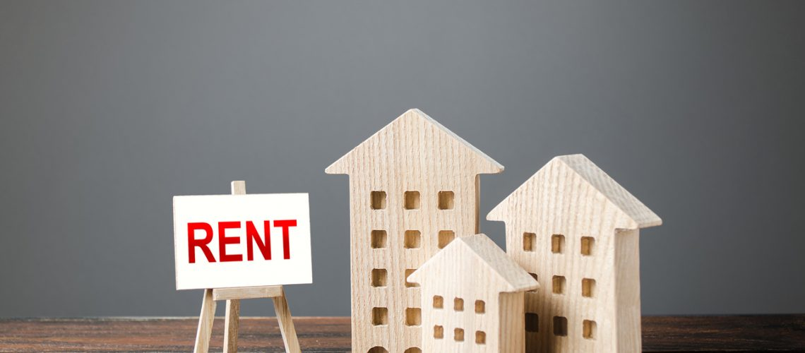 Three figures of houses and an easel with the word rent. Realtor services, search for optimal options. The concept of temporary rental housing and real estate. The choice between renting and buying.